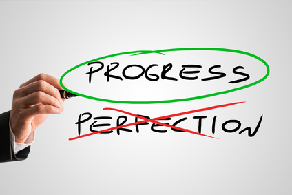 Progress - Perfection concept with a businessman crossing through the handwritten word Perfection in red while ringing Progress in green conceptual of sacrificing perfection to develop and progress.