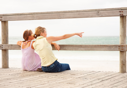 Rear view of a mother and daughter at the beach sitting by a wooden railing, woman pointing away